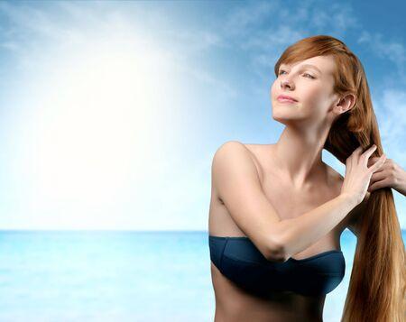 personas tomando agua: bella mujer con el cabello largo tomando sol en el mar