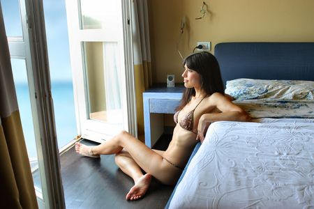 attractive girl in bikini looking the sea from her bedroom photo