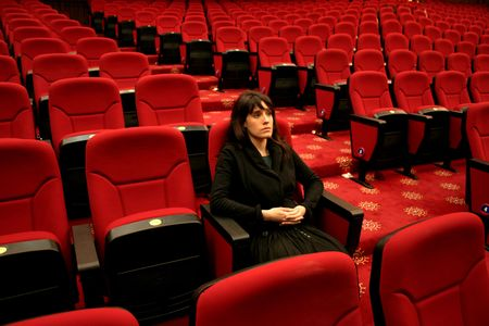 delusion: woman seated alone in a cinema interior