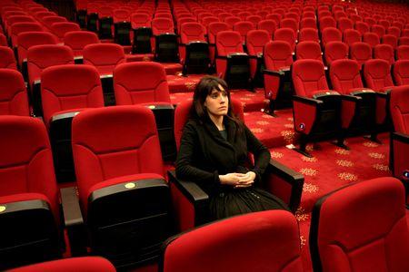 critic: woman seated alone in a cinema interior