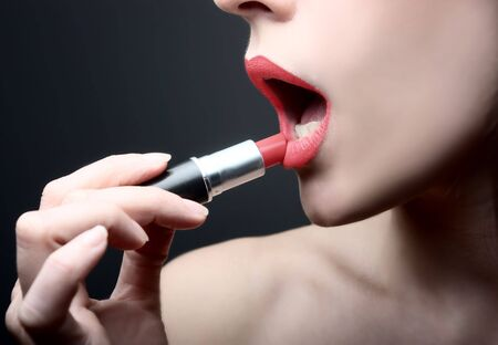 closeup of hand putting lipstick on mouth Stock Photo - 5655274