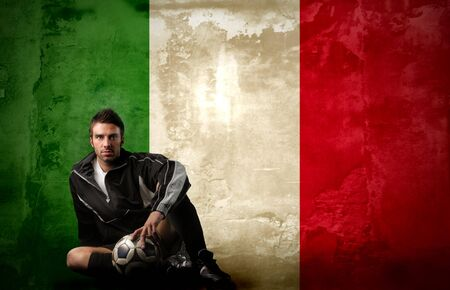 italian soccer player sitting against a italian flag background Stock Photo