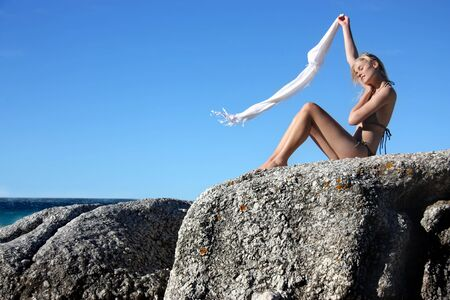 blond girl in bikini on sea rocks with flying foulard photo