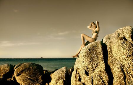 pretty young woman seated on sea rocks Stock Photo - 5691181