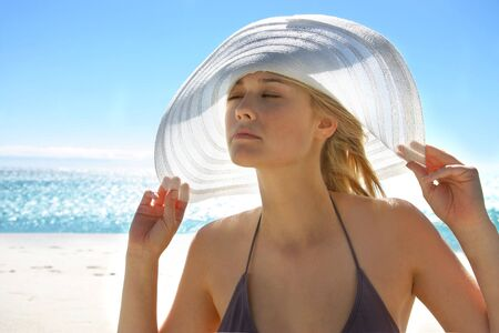 sun protection: beautiful girl in bikini with hat at the sea Stock Photo