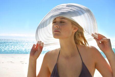 personas tomando agua: bella muchacha en bikini con el sombrero en el mar Foto de archivo
