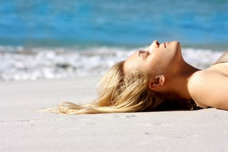 portrait of beautiful woman with long blond hair on the beach photo