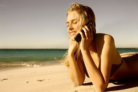 promoter: beautiful blond girl talking at mobile phone on the beach  Stock Photo