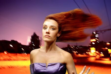 elegant woman with flying hair and a city at night photo