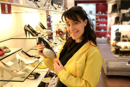 shoe shelf: pretty girl buying a pair of shoes