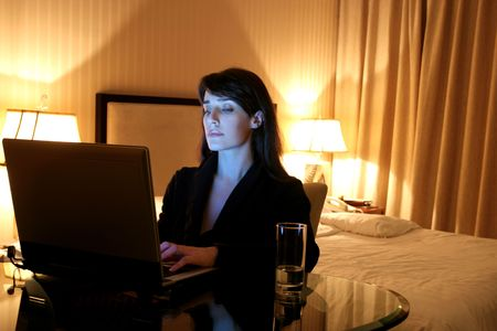 luxury hotel room: business woman  using laptop in a hotel room