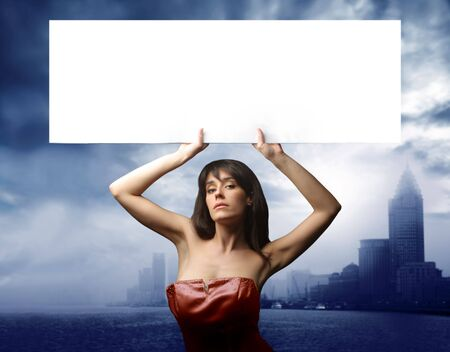 elegant woman holding a white  banner with modern city on the background photo