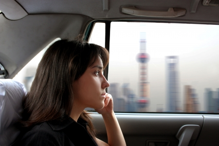portrait of attractive woman seated in a taxi and looking at chinese city photo