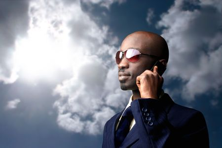 businessman talking: black businessman talking at mobile against a sunny sky Stock Photo