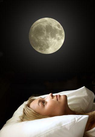 insomnio: retrato de la bella muchacha en una almohada mirando la luna