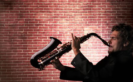 young man playing saxophone against a brick wall  photo