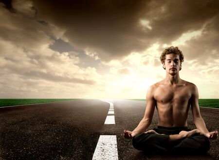 young man practice yoga on a country road photo