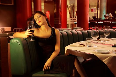portrait of a young woman drinking wine in a restaurant  photo