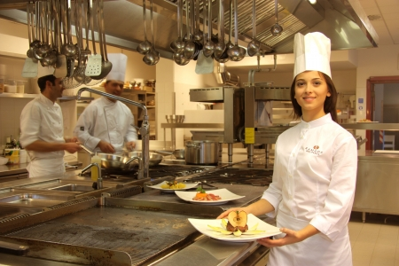 inox: young cook in a kitchen of a restaurant