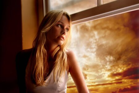 portrait of a beautiful young woman at window  photo