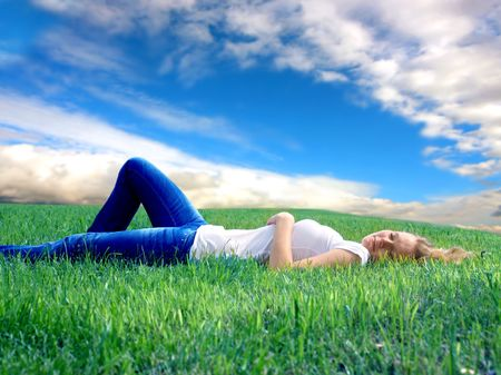 lawn area: blond girl laying on grass field Stock Photo