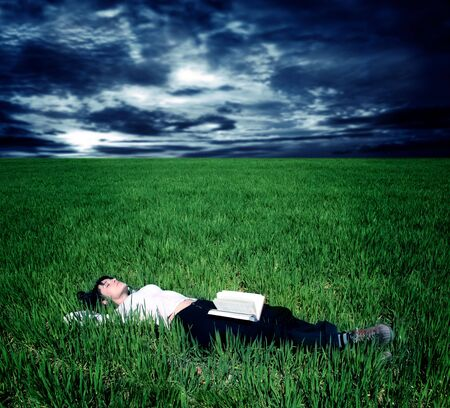 young woman lying in a grass field with a book and a stormy sky photo