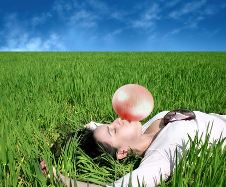 pretty girl lying on grass and blowing a bubblegum photo