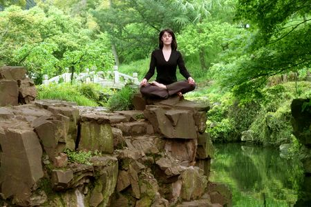 beautiful woman practicing yoga in a oriental garden photo