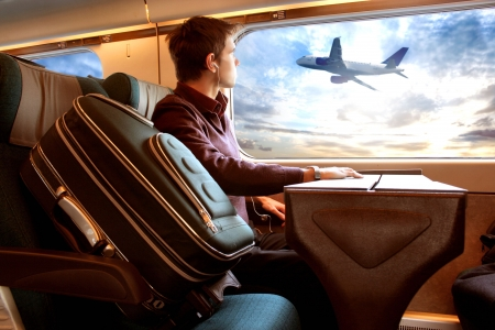 business traveler:  man on the train looking sunset and airplane