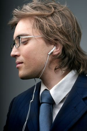 portrait of businessman listening music with podcast photo