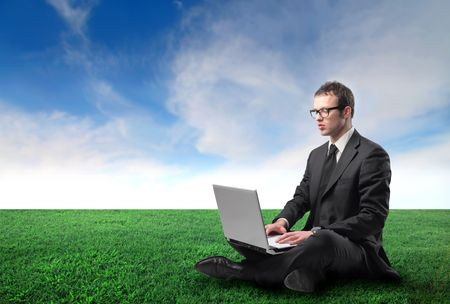 Businessman sitting on a green meadow and working on a laptop photo