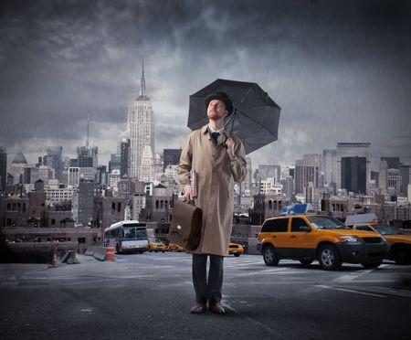 lluvia paraguas: Caballero con paraguas de pie en medio de una calle de la ciudad  Foto de archivo