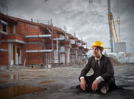 house worker: Businessman with helmet sitting in a construction site