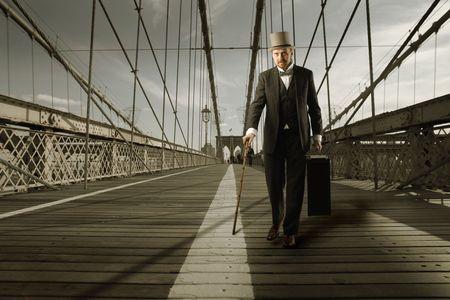 Gentleman with cylinder hat crossing a bridge photo