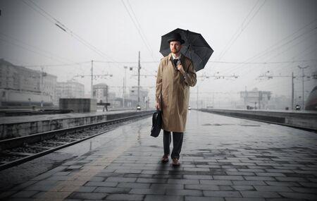 UOMO pioggia: Gentiluomo con ombrello in piedi su una piattaforma di una stazione ferroviaria