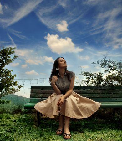banc de parc: Jeune femme assise sur un banc de parc