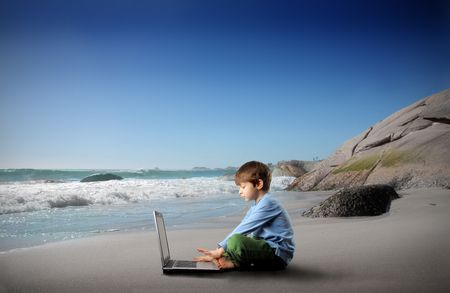 Child sitting on a beach and using a laptop Stock Photo - 6628080