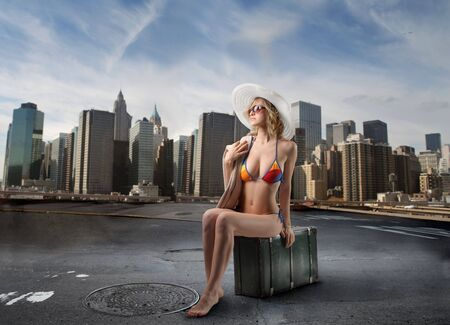 Young woman in swimsuit sitting on a suitcase with cityscape on the background photo
