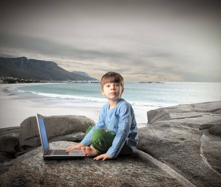 Child sitting on a rock at the seaside and using a laptop photo