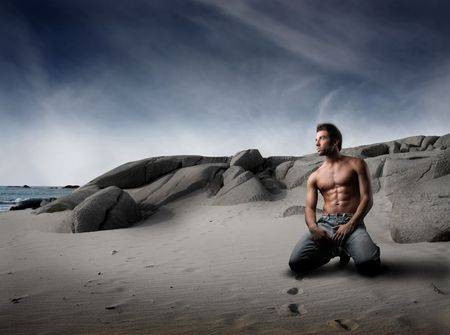 Young bare-chested man kneeling on a beach photo