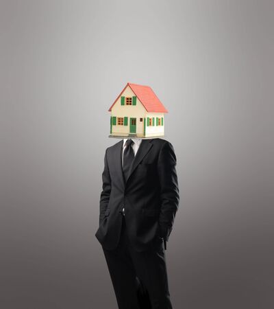 vend: Businessman with the model of a house instead of his head Stock Photo
