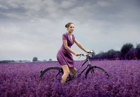 Beautiful woman in violet reading a bike on a lavender field