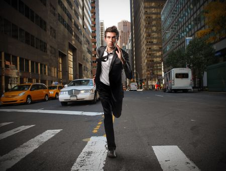 Businessman running on a city street photo