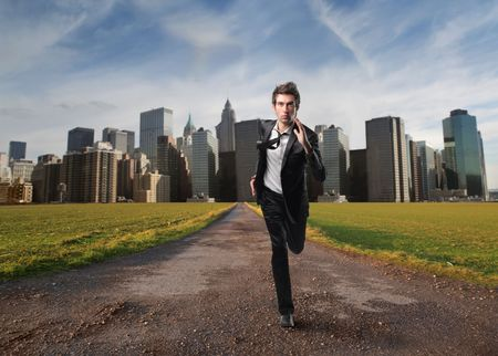 new path: Businessman running away from a city Stock Photo