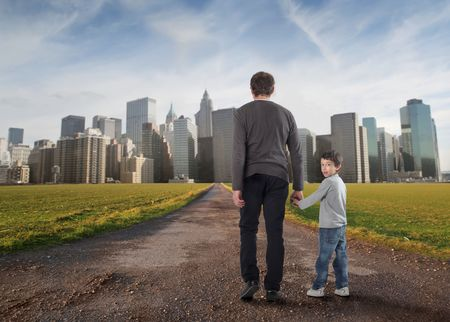 healthy path: Father and son hand in hand walking on a road to a city