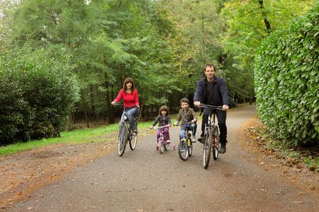 Happy family riding bicycles in a park photo