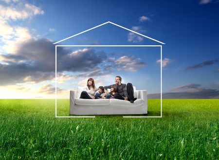 green couch: Smiling family sitting on a sofa surrounded by the form of a house on a green meadow