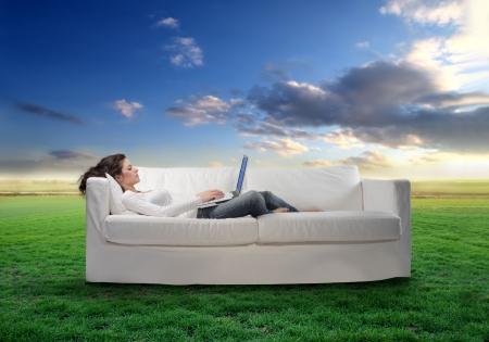lying in grass: Joven mujer recostada en un sof� con un equipo port�til con verde pradera en el fondo