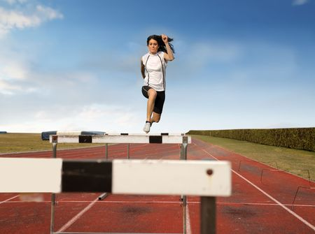 young girl feet: Woman jumping an obstacle on a running track Stock Photo