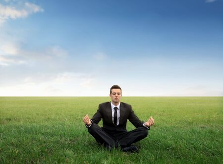 positions: Businessman meditating on a green meadow Stock Photo